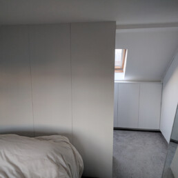 A walk-in loft storage area designed, built and installed by Cook Joinery, London.
